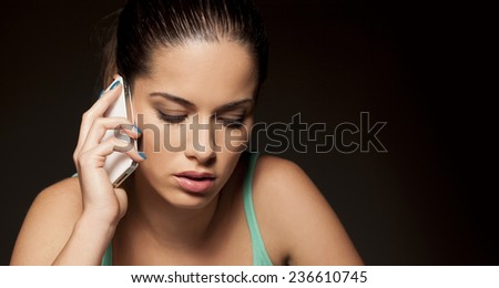 portrait of a beautiful woman who is talking on the phone on a dark background - stock photo