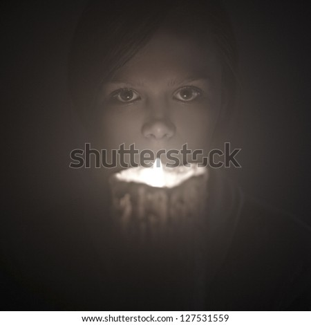 portrait of a beautiful woman with a candle on a black background - stock photo