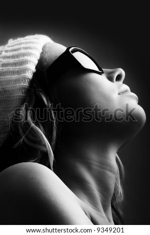 portrait of a beautiful woman with a cap and some sunglasses against grey background - stock photo