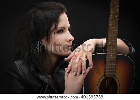 Portrait of a beautiful woman with a guitar