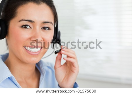Portrait of a beautiful woman with a headset helping customers while sitting at the office - stock photo