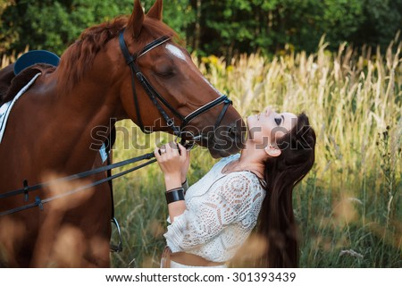 Portrait of a beautiful woman with a horse on nature - stock photo