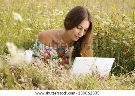 Portrait of a beautiful woman with a laptop lying on the grass - stock photo