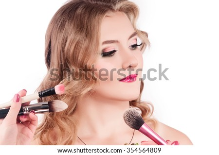 Portrait of a beautiful woman with a make up brush - stock photo