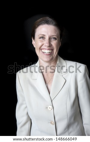 Portrait of a beautiful woman with a nice smile in a business suit shot on a black background. - stock photo