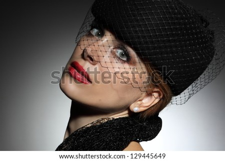 portrait of a beautiful woman with an elegant hat - stock photo