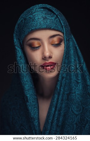 Portrait of a beautiful woman with arabian makeup in paranja isolated on dark background - stock photo