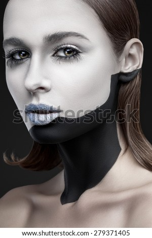 Portrait of a beautiful woman with black and white make-up on a gray background - stock photo