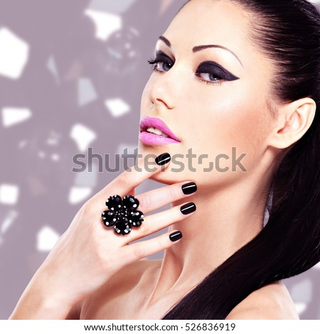 Portrait of a beautiful  woman with black nails and bright makeup.