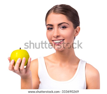 Portrait of a beautiful woman with braces on the teeth eating green apple, isolated on a white background - stock photo