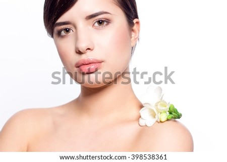 Portrait of a beautiful woman with clean skin on a white background. The woman's face on a white background. A woman holding a white flower.