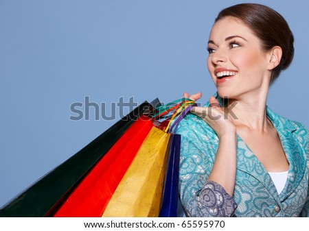 Portrait of a beautiful woman with colored shopping bags isolated on blue - stock photo
