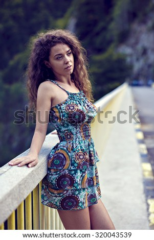 portrait of a beautiful woman with curly hair in nature