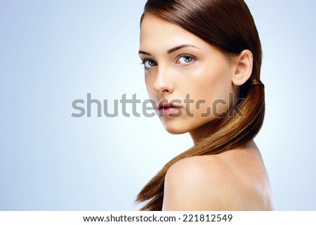 Portrait of a beautiful woman with cute face on blue background - stock photo