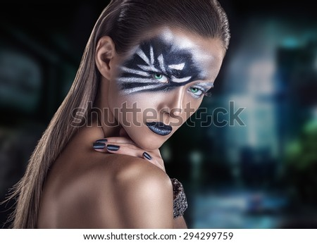 Portrait of a beautiful woman with fashion make-up and black nail polish on background blurred city - stock photo