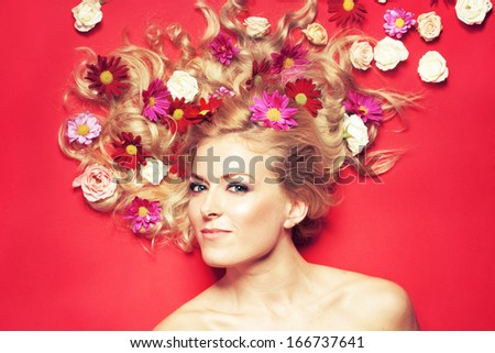 Portrait of a beautiful woman with flowers in her hair against red background  - stock photo