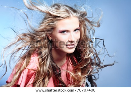 Portrait of a beautiful woman with flying hair. Studio shot over grey background. - stock photo