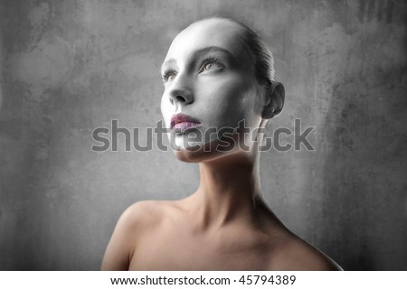 Portrait of a beautiful woman with her face colored with white - stock photo