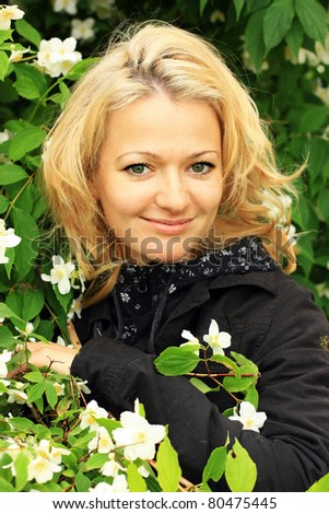 Portrait of a beautiful woman with jessamine bush outdoors