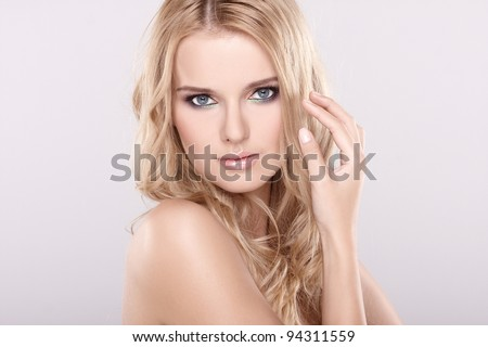 Portrait of a beautiful woman with long blonde hair on white background
