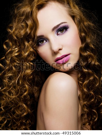 Portrait of a beautiful  woman with  long curly hairs - isolated on black background - stock photo