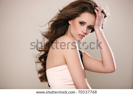Portrait of a beautiful woman with long flying hair, isoleted on beige background - stock photo