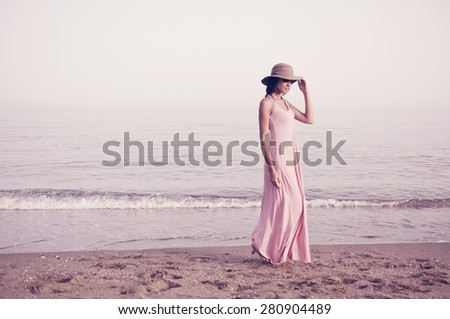 Portrait of a beautiful woman with long pink dress and sun hat on a tropical beach