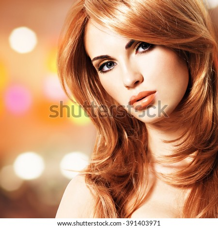 Portrait of a beautiful woman with long straight red hair.