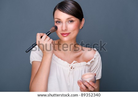 Portrait of a Beautiful woman with makeup brush near her face looking at camera and smiling against grey background - stock photo