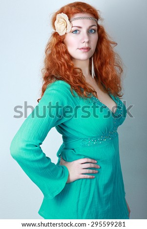 portrait of a beautiful woman with red curly hair. wearing a romantic green or turquoise dress. Fashion blue toning - stock photo