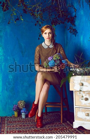 portrait of a beautiful woman with red hair in curly braided hairstyle. wearing a romantic lace dress with red boots on grunge blue background  - stock photo