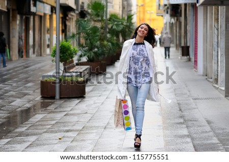 Portrait of a beautiful woman with shopping bags walking along a commercial street - stock photo