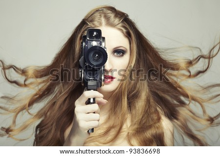 Portrait of a beautiful woman with the camera. Fashion photo - stock photo