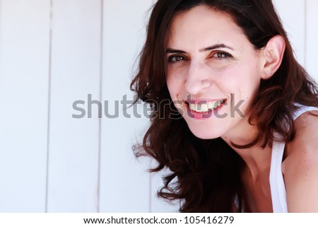 portrait of a beautiful 35 year old girl on a background of vintage white fence - stock photo