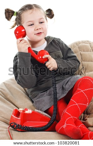 Portrait of a beautiful 3-year-old girl, wearing green top, red tights and grey skirt, playing with a red retro telephone, speaking into the receiver, smiling - isolated on white - stock photo