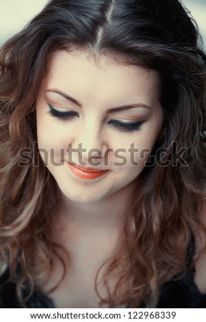 Portrait of a beautiful 20 year old woman looking down.