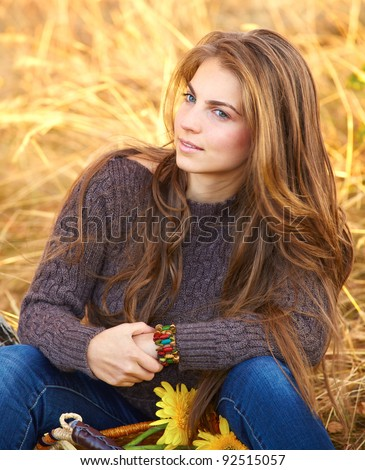 Portrait of a beautiful 20 year old young woman outdoor during autumn season. - stock photo