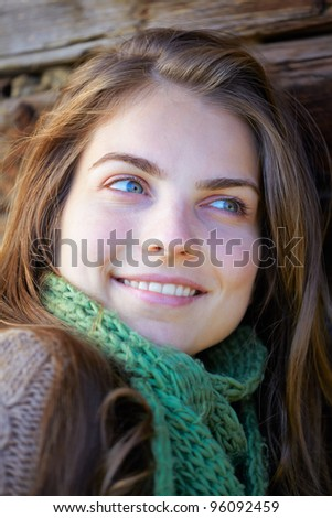 Portrait of a beautiful younf woman sitting at the shade outdoor. - stock photo