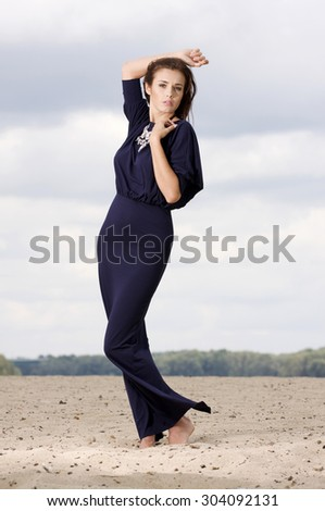 Portrait of a beautiful young adult attractive sexy and sensuality pretty brunette woman in violet elegance fashionable dress on the beach - stock photo