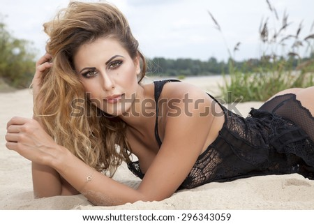 Portrait of a beautiful young adult attractive sexy and sensuality pretty brunette woman wearing black blouse shirt on the beach - stock photo