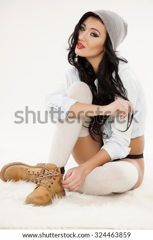 portrait of a beautiful young adult sensuality brunette woman in grey cab and socks, brown shoes and blue jeans shirt on white background