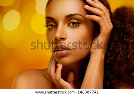 Portrait of a beautiful young African woman gently touching her face. - stock photo
