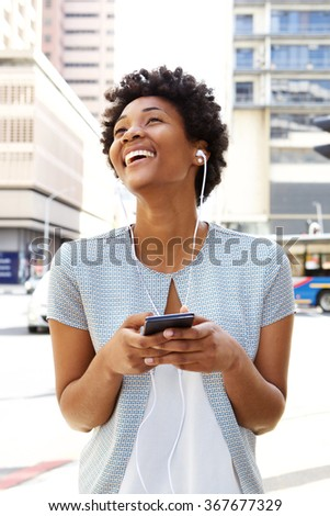Portrait of a beautiful young african woman listening music with earphones on city street  - stock photo