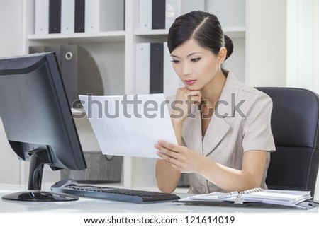 Portrait of a beautiful young Asian Chinese woman or businesswoman in office reading paperwork and using a computer - stock photo