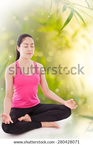 Portrait of a beautiful young asian (thai) woman practicing yoga on natural blurred bokeh abstract from bamboo leaf, sitting in a lotus position. - stock photo
