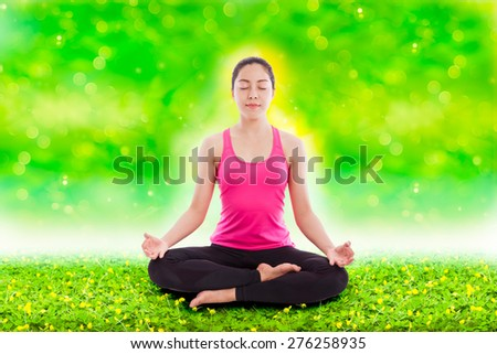 Portrait of a beautiful young asian (thai) woman practicing yoga with aura over body, sitting in a lotus position over green clover and blurred bokeh abstract background