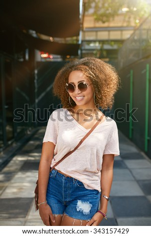 Portrait of a beautiful young black woman wearing sunglasses smiling at camera. African young female in casuals posing outdoors. - stock photo
