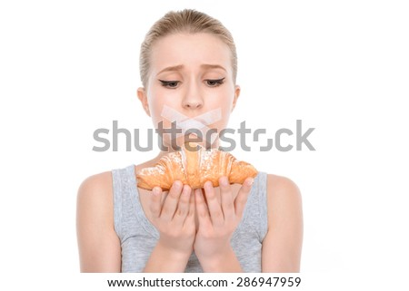 Portrait of a beautiful young blond fit girl wearing a grey top holding a croissant in her hands looking at it sadly, her mouth sealed with tape, isolated on a white background - stock photo