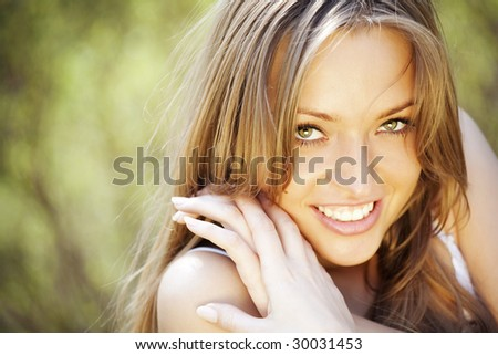 Portrait of a beautiful young blond lady smiling - stock photo