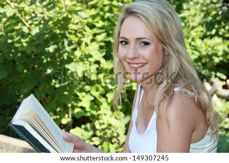 Portrait of a beautiful young blond woman reading a book outdoors in front of leafy greenery looking at the camera with a smile - stock photo